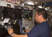 Thumb leroy chiao working on space station remote manipulator system
